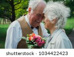 old couple is walking in the... | Shutterstock . vector #1034422423