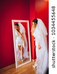 bride looks at herself in the... | Shutterstock . vector #1034455648
