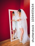 bride looks at herself in the... | Shutterstock . vector #1034455654