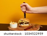 hand stabbing with knife burger ... | Shutterstock . vector #1034522959