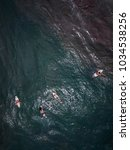 Small photo of The surfer rides and swims on the board dissecting the waves of the ocean. Deep and boundless ocean. Aerial view with copy space.