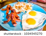 Small photo of Closeup of large breakfast brunch plate with fried eggs, hash browns shredded potatoes, sausage tako octopus, blue plate