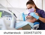 female dentist drilling tooth... | Shutterstock . vector #1034571070