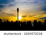 people watch the sunset by the... | Shutterstock . vector #1034573218