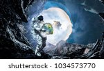 spaceman carry his mission.... | Shutterstock . vector #1034573770