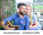 Small photo of Girl with happy face fall in love with bearded man, couple reads poems. Romantic couple holds old books with poems. Couple in love sit in cafe outdoor, nature background. Romantic date concept.