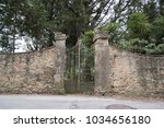 old iron gate in stone walls in ... | Shutterstock . vector #1034656180