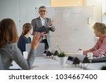 teacher giving economics class  ... | Shutterstock . vector #1034667400