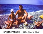 Small photo of USSR, ABKHAZIA, BLACK SEA - CIRCA 1980: Vintage photo of father with little son on Black sea beach in Abkhazia, USSR