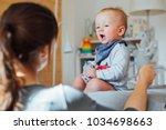 unrecognizable mother pulling... | Shutterstock . vector #1034698663