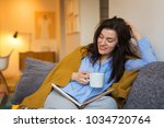 brunette woman sitting on sofa  ... | Shutterstock . vector #1034720764