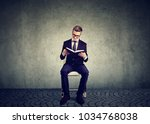 Small photo of Young diligent man in suit sitting on chair and reading book in eyeglasses.
