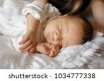 newborn sleeps tightly with... | Shutterstock . vector #1034777338