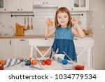 little girl shows painted eggs... | Shutterstock . vector #1034779534