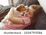 Stock photo jack russell terrier puppy licks little child s face portrait of a little girl hugging a puppy at 1034793586