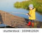 Little Boy Catching A Fish Fro...