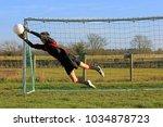 teenage boy goalkeeper saving a ... | Shutterstock . vector #1034878723