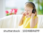 cute little girl wearing huge... | Shutterstock . vector #1034884699