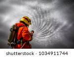 firefighter using extinguisher... | Shutterstock . vector #1034911744
