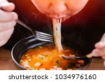 man eating very hot and spicy... | Shutterstock . vector #1034976160