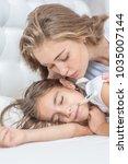 mother kisses her daughter's... | Shutterstock . vector #1035007144