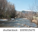 Small photo of Wooden bridge over a river. Beautiful Altaic landscape with snow-capped mountains, sky and clouds. River crossing to the mountains.