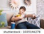 overweight boy watching tv with ... | Shutterstock . vector #1035146278