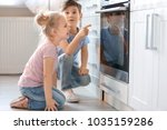 little kids sitting near oven... | Shutterstock . vector #1035159286
