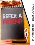 Small photo of Word, writing Refer A Friend. Business concept for Referral Marketing Written on notebook book, wooden background with sticky sunglasses and red pen