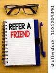 Small photo of Handwriting Announcement text showing Refer A Friend. Business concept for Referral Marketing Written on tablet, wooden background with sticky note and pen