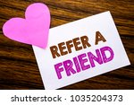 Small photo of Conceptual hand writing text showing Refer A Friend. Concept for Referral Marketing written on sticky note paper, wooden background. With pink heart meaning love adoration.