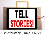 Small photo of Handwriting Announcement text showing Tell Stories. Business concept for Storytelling Telling Story Written on shopping bag and tablet white background, tablet charging.