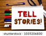 Small photo of Word, writing Tell Stories. Business concept for Storytelling Telling Story Written on notebook, wooden background office equipment like pens scissors colourful marker