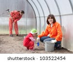 Happy women with child works at hothouse in spring - stock photo