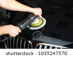 the worker polishes a car cowl... | Shutterstock . vector #1035247570