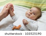 Adorable baby holding mother hand. - stock photo
