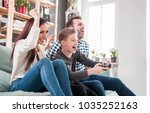excited family playing video... | Shutterstock . vector #1035252163
