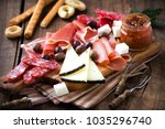 Small photo of Cured meat and cheese platter of traditional Spanish tapas - chorizo, salsichon, jamon serrano, lomo and slices of goat cheese - served on wooden board with olives and bread sticks