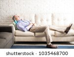 man in his 50s lying on sofa at ... | Shutterstock . vector #1035468700