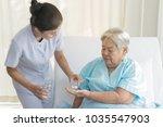 caregiver nurse helping elderly ...   Shutterstock . vector #1035547903