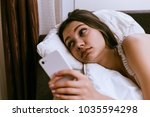 sad woman lies on the bed under ... | Shutterstock . vector #1035594298