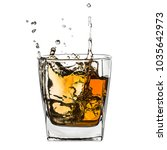 Glass of splashing whiskey with ice isolated on white