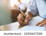students writing pen in hand... | Shutterstock . vector #1035647200