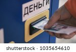 Small photo of Person's hand sticks a paper money bill into the banknote bill acceptor. Clip. Bill acceptor