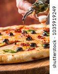 chef pouring olive oil on pizza. | Shutterstock . vector #1035919249