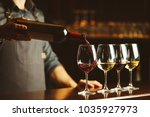 Stock photo bartender pours red wine in glasses on wooden bar counter 1035927973