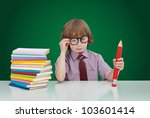 Boy genius with books and large pencil adjusting his glasses - on green background - stock photo