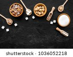 Small photo of Brown and white sugar in bowls, scoop and spoon. Cane, refind, granulated, cubes, candy. Black background top view copy space