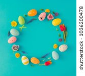 Small photo of Creative Easter layout made of colorful eggs and flowers on blue background. Circle wreath flat lay concept.