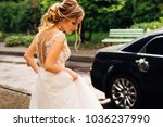 Stock photo incredible bride in white wedding dress and with a beautiful hairstyle goes to decorated black car 1036237990